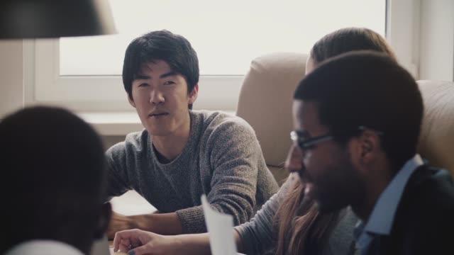 幸せな自信を持って日本の若いフリーランスのビジネスマンは、アイディアを共有、スローモーションを満たす多民族のオフィスで笑顔 - 東アジア点の映像素材/bロール