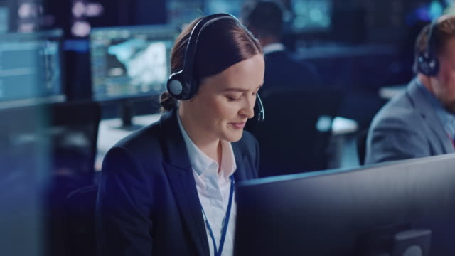 happy confident technical customer support specialist having a headset call while working on a computer in a dark monitoring and control room filled with colleagues and display screens. - call center стоковые видео и кадры b-roll