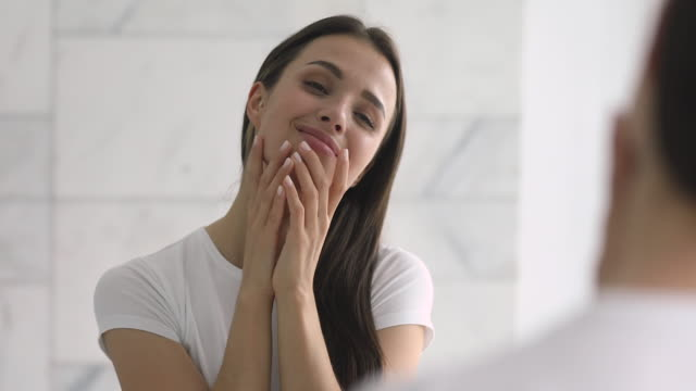 stockvideo's en b-roll-footage met gelukkig vertrouwen jonge vrouw aanraken gezicht huid kijken in spiegel - mirror mask