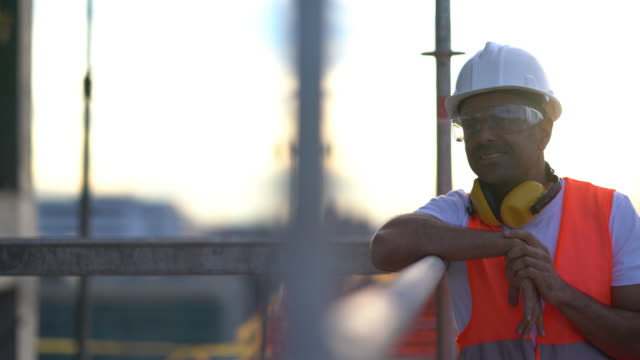 happy construction worker leaning on a scaffold looking away pensive and smiling - occhiali protettivi video stock e b–roll