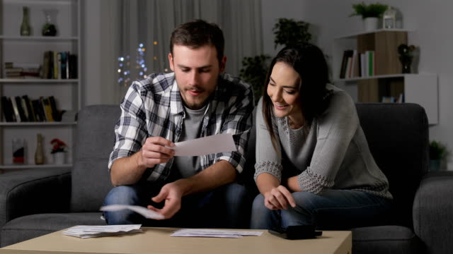Happy couple accounting checking receipts in the night