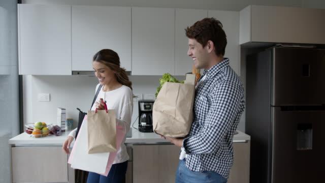 食料品の買い物の話と笑顔の後に家に到着幸せなカップル - 荷物をとく点の映像素材/bロール