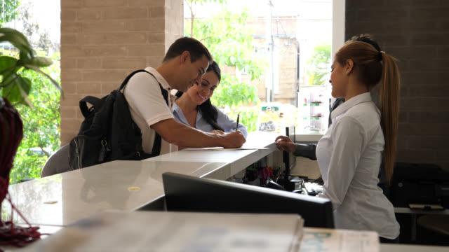 mutlu çift otelde resepsiyonist ve yöneticisi için ön masada bir formu doldururken konuşmak için gelen - hotel reception stok videoları ve detay görüntü çekimi