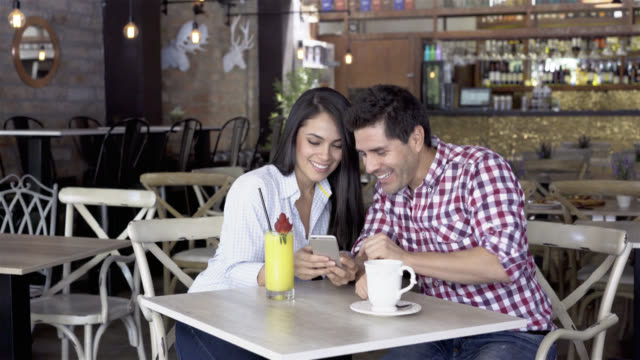 Happy couple at a cafe looking at social media and laughing video