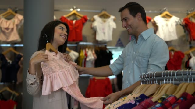 Happy couple at a store looking at clothes and walking towards camera while woman shows partner something she liked Happy couple at a store looking at clothes and walking towards camera while woman shows partner something she liked both smiling department store stock videos & royalty-free footage