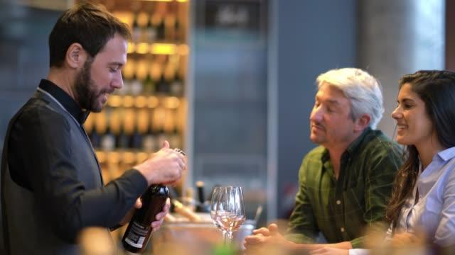 와인 시음 전문적인 감정에 얘기 하는 그 와인을 여는 동안 모든 미소에서 행복 한 커플 - 와인병 스톡 비디오 및 b-롤 화면