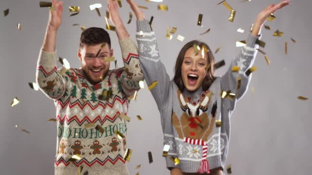 happy couple at christmas party under confetti