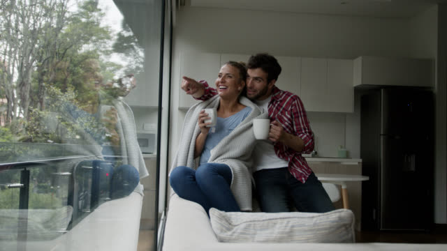 Happy couple at home enjoying a warm tea on a cold day looking at the window view talking Happy couple at home enjoying a warm tea on a cold day looking at the window view talking and smiling blanket stock videos & royalty-free footage