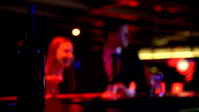 Happy couple at nightclub, drunk man falling on bar counter, breakup depression video