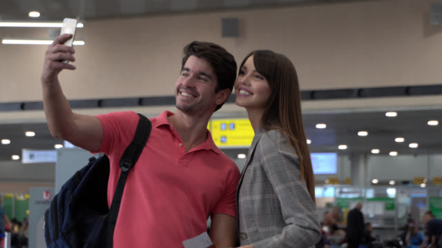 Happy couple at the airport taking a selfie with a smartphone and looking at it smiling