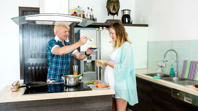 Happy couple at the kitchen in the morning. Pregnant wife. Breakfast. video