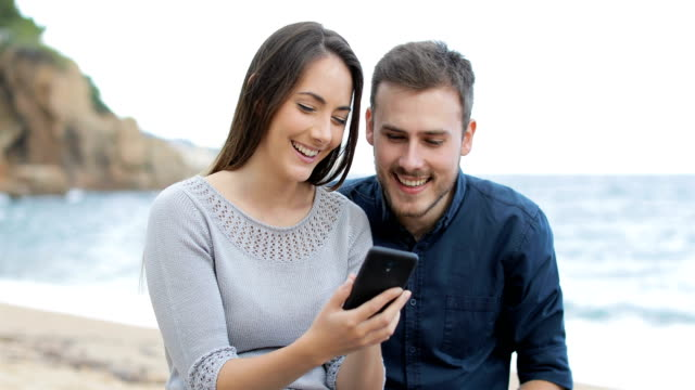 Happy couple browsing phone on the beach