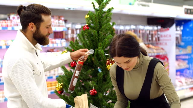 A happy couple buys groceries for Christmas at the grocery store. Slow motion.