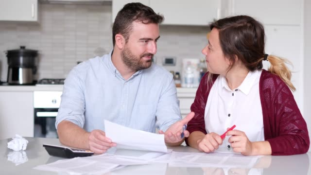 happy couple calculating home bills - risparmi video stock e b–roll