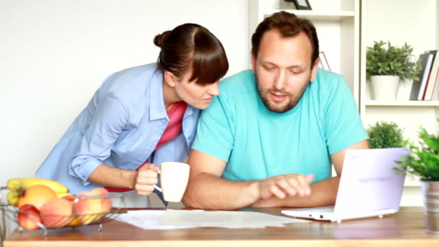 Happy couple calculating their bills by the table at home video