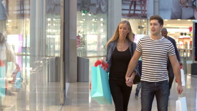 Happy Couple Carrying Bags In Shopping Mall video