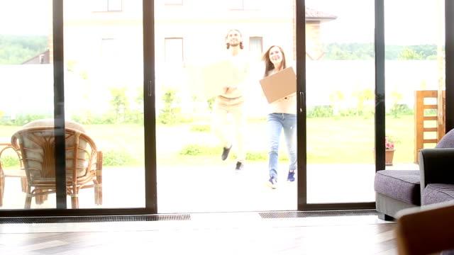 Heureux couple porte boîtes entrant dans une maison neuve, propriétaires de maisons mobiles - Vidéo