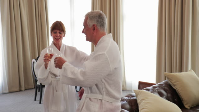 Happy Couple Celebrate Anniversary in Hotel Mature couple are kissing in their hotel room with a glass of champagne. They are both wearing dressing gowns. falling in love stock videos & royalty-free footage