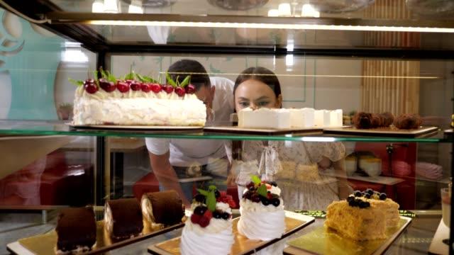 coppia felice sceglie gustose torte in vetro show case di negozio - dolci video stock e b–roll