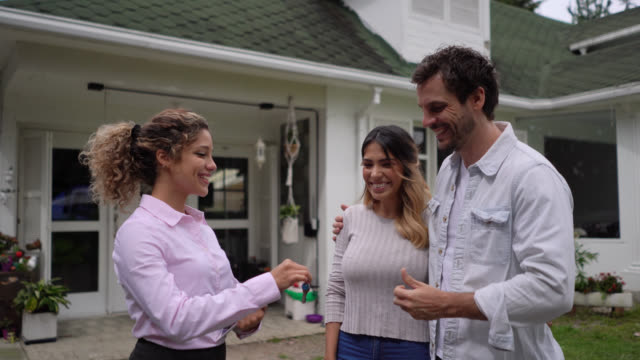 Happy couple closing a deal with female realtor at a property smiling while receiving the keys
