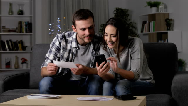 Happy couple comparing receipts online on phone