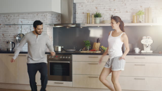 Happy Couple Creatively Dances in the Kitchen. Both are Adorable and Smiling.
