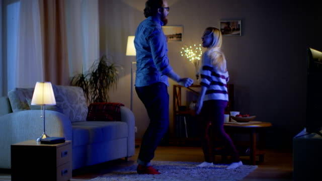 Happy Couple Dances in Their Living Room with TV Turned On. Their House is Cozy and Warm. It's Evening. video