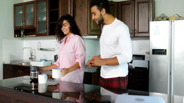 L'heureux Couple dansant dans cuisine matin, café Pour fille, jeune homme joyeux et femme tenant la coupe - Vidéo