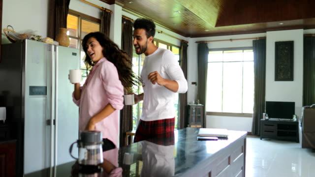 Heureux Couple dansant dans cuisine matin, jeune gai homme et femme tenant la tasse à café - Vidéo