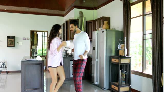 L'heureux Couple dansant dans cuisine matin, jeune homme joyeux et femme tenant la tasse avec du café en Studio Appartement moderne - Vidéo