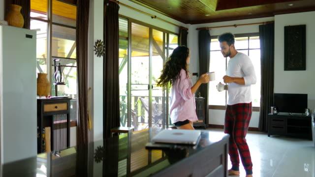 Heureux Couple danse matin, gai jeune homme et femme tenant la tasse avec du café en Studio Appartement moderne - Vidéo