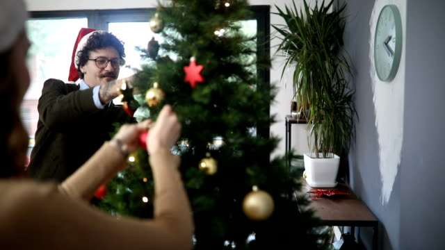 幸せなカップル飾るクリスマス ツリー - サンタの帽子点の映像素材/bロール