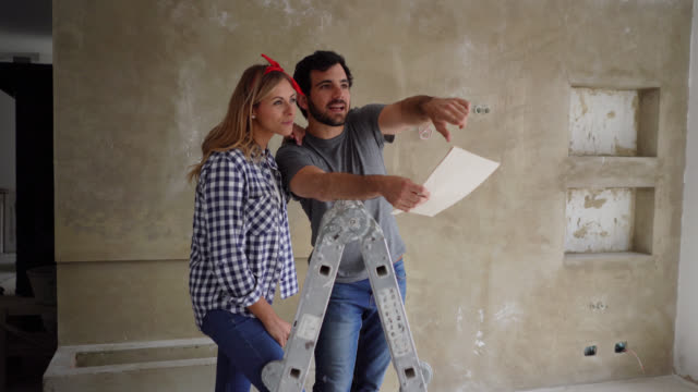 Happy couple doing a home renovation looking at a design on paper while pointing at a wall and talking Happy young couple doing a home renovation looking at a design on paper while pointing at a wall and talking renovation stock videos & royalty-free footage