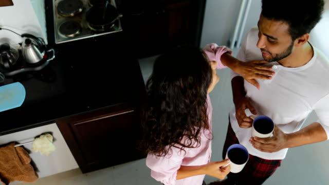 L'heureux Couple boire un café dans la cuisine matin parler vue d'Angle au sommet, jeune homme joyeux et femme tenant des tasses - Vidéo