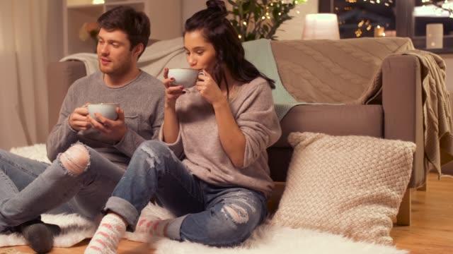 vídeos de stock, filmes e b-roll de casal feliz bebendo chocolate quente com marshmallow em casa - chocolate quente