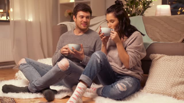 vídeos de stock e filmes b-roll de happy couple drinking hot chocolate with marshmallow at home - hygge