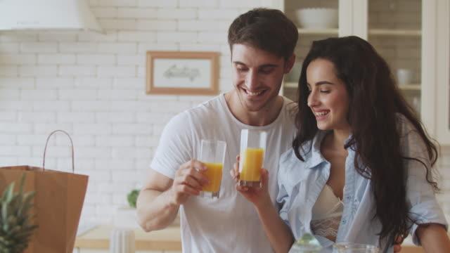 vídeos y material grabado en eventos de stock de feliz pareja bebiendo jugo de naranja en la cocina. pareja de primer plano coqueteando en casa. - zumo