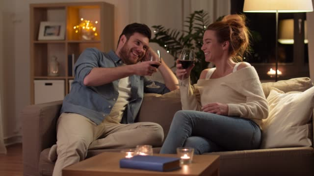 vídeos de stock e filmes b-roll de happy couple drinking red wine at home in evening - hygge