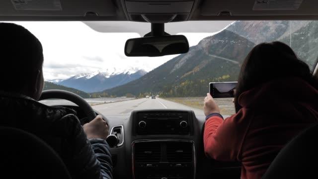 Gelukkig paar rijden en het gebruik van de telefoon voor overneemt foto landweg in de Winter, reizen video