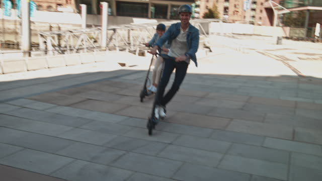 happy couple driving electric push scooters - monopattino elettrico video stock e b–roll