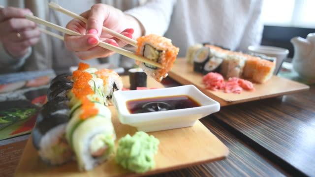 happy couple eating sushi rolls in japan restaurant - sushi stock videos and b-roll footage