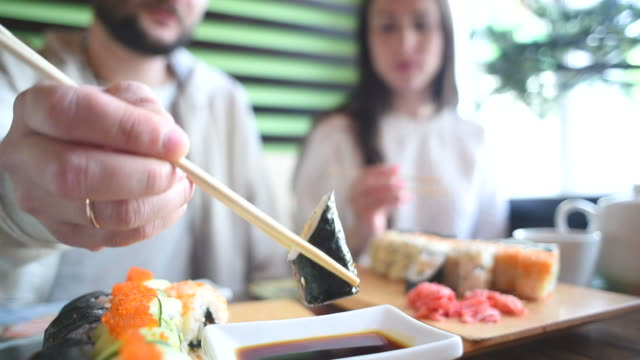 Happy couple eating sushi rolls in japan restaurant video