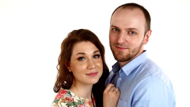 happy couple embracing and looking camera on white background - pochodzenia rosyjskiego filmów i materiałów b-roll