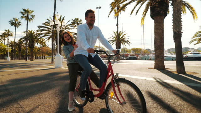 Happy couple enjoying a bicycle ride together. Playful couple enjoying beautiful moments together while visiting by bike Barcelona. Slow motion scene. life balance stock videos & royalty-free footage