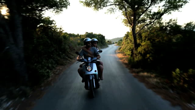 Happy couple enjoying scooter adventure video