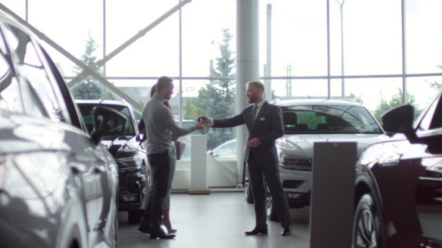 Happy Couple Getting Key to New Car in Auto Showroom Joyous couple talking with sales manager in auto showroom, receiving key and walking to their new car car salesperson stock videos & royalty-free footage