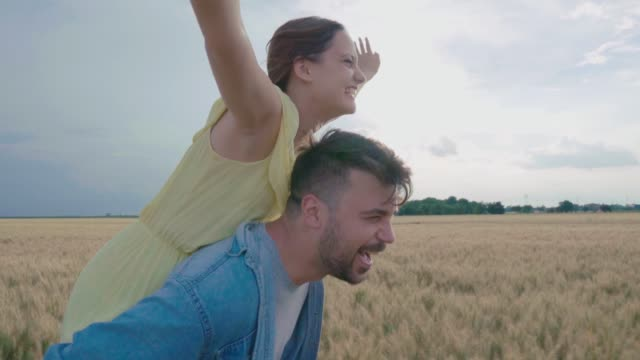Happy couple having fun in a wheat field Happy couple heaving fun in a wheat field on a sunny summer day falling in love stock videos & royalty-free footage
