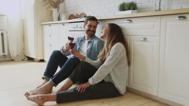 Happy couple hold glasses drink wine sit on kitchen floor