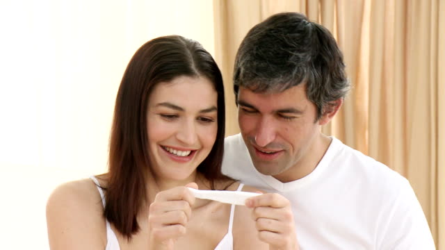 Happy couple holding a pregnancy test video
