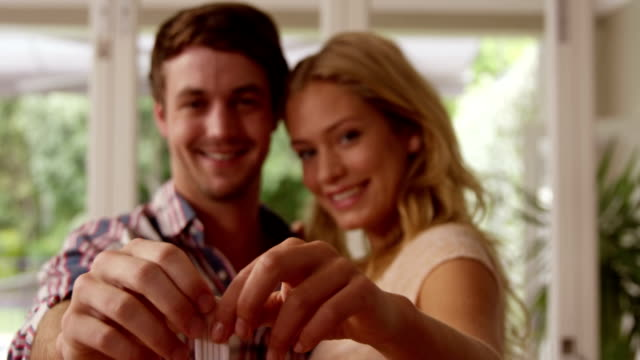 happy couple holding keys together - new home stock videos and b-roll footage
